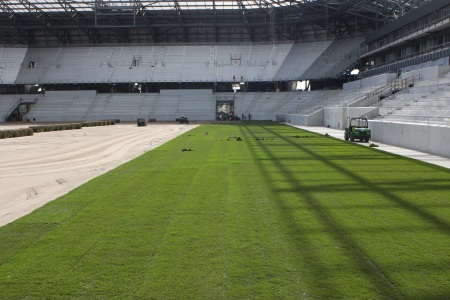 The first rolls of sod were laid in place.